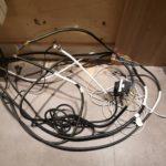 Des câbles électriques à nus derrière un meuble